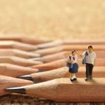 鉛筆の上に座って語り合っている学生服の二人
